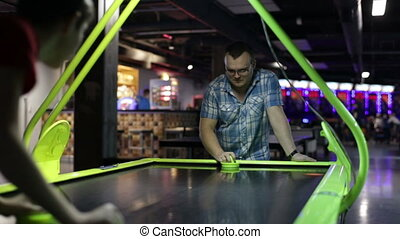 Adult man playing air hockey game