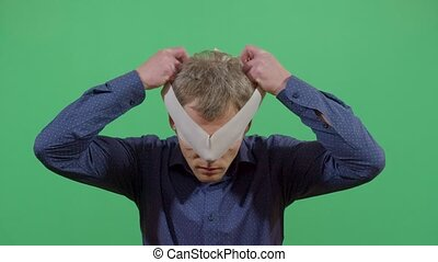 Adult Man Putting On A Blindfold Like Hiding From The World. Studio Isolated Shot Against Green Screen Background