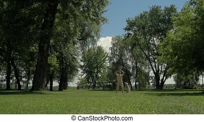Adult man throwing the rubber ball for his dog - Day for...
