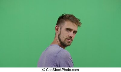 Adult Man Turning Around To See The Viewer Disclosing His Or Her Identity. Studio Isolated Shot Against Green Screen Background