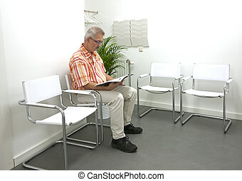 adult man waiting in waitingroom - adult male reading a book...
