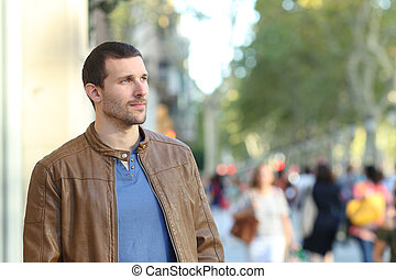 Adult man walking looking away in the street
