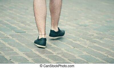 Adult man wearing shorts walks on cobblestone pavement