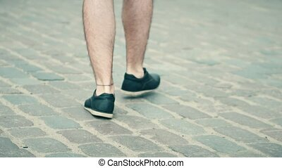 Adult man wearing shorts walks on cobblestone pavement
