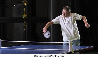 Close-up of focused, mature male with cerebral palsy skillfully playing ping-pong. Disabled man sincerely smiling after successful hit, positive emotions, socializing activity