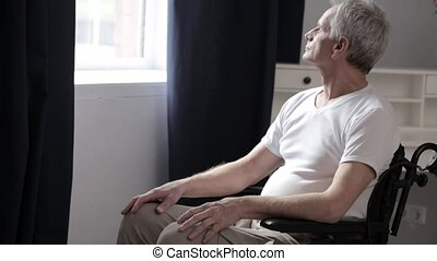 Adult Man with Gray hair in a Wheelchair in Hospital. - A...