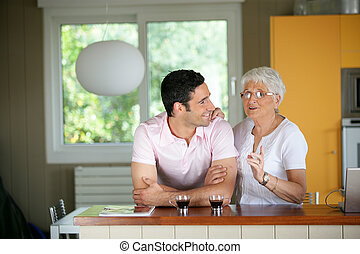 Adult man with his mother in a kitchen