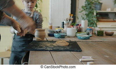 Adult man's hands working with clay in pottery studio while ...