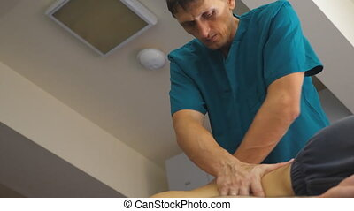 Adult masseur massaging back of young athlete in a parlor....