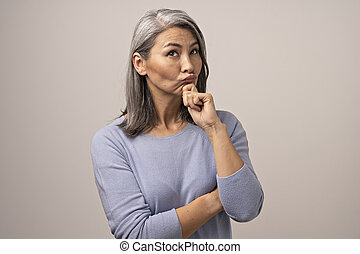 Adult Mongolian Woman with Gray Hair on a Gray Background.