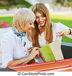 Adult mother and daughter are considering buying after shopping.