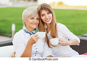 adult mother and daughter drinking tea or coffee and talking outdoors