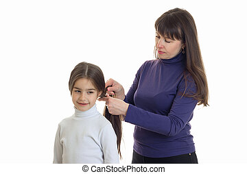 Adult mother makes a hairstyle to her little daughter
