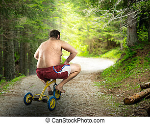 Adult naked man cycling on child's bicycle - Adult naked man...