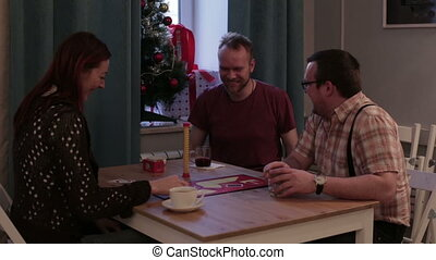 Adult people play a board game in a cafe
