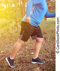 adult plump athlete in blue uniform, sneakers and black shorts runs through the middle of the woods