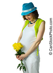 Adult pregnant woman in the studio with a yellow flower