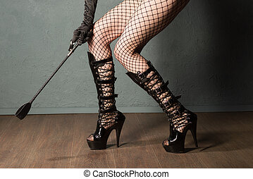Adult sex games. Sexy girl legs in fishnet and high heels fetish boots with whip prepare for punishment. - image