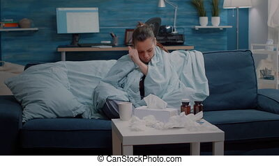 Adult shivering and feeling cold while using blanket and drinking tea for warmth. Woman with disease having chills and holding cup with hot beverage to cure coronavirus symptoms.