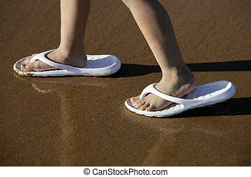 Adult shoes for children feet on beach sand outdoor