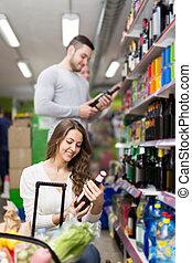 shoppers choosing bottle of wine at liquor store