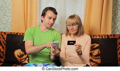 Adult son and elderly mother making online banking with credit card by phone.