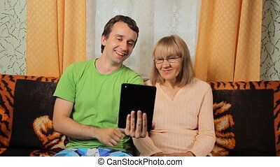 Adult son and elderly mother making video call with the tablet. Mother and son smiling sitting at home on a sofa