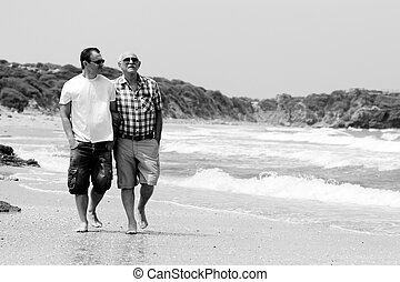 adult son and father walking together on the beach