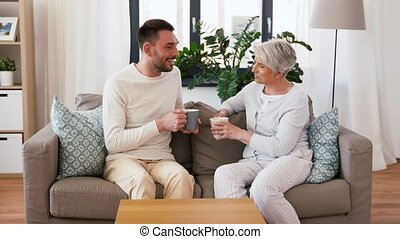 adult son and senior mother drink coffee at home - family,...