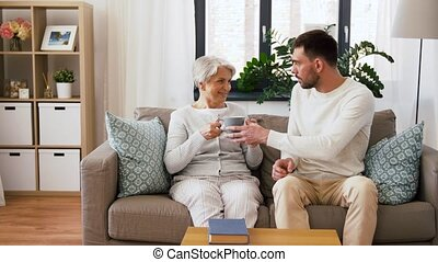 family, generation and people concept - happy smiling adult son bringing coffee to senior mother reading book at home