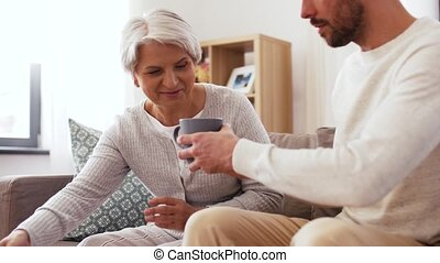 adult son bringing coffee to senior mother at home - family,...