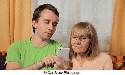 Adult son teaching elderly mother to work for the telephone. Mother and son smiling at home on sofa