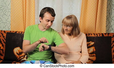 Adult son teaching elderly mother to work with smart watches. Mother and son smiling sitting at home on a sofa