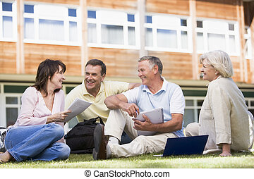 Adult students on lawn of school studying and talking