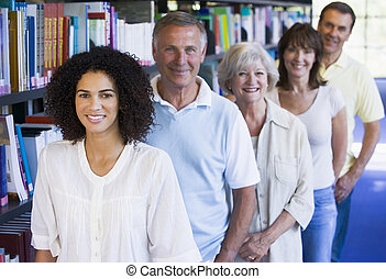 Adult students standing in a library