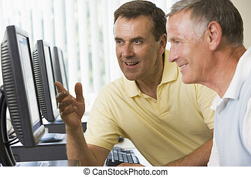 Adult students working on computers together