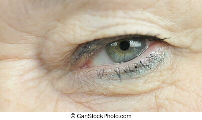 Adult woman blinking one eye. Close up - Adult woman aged...