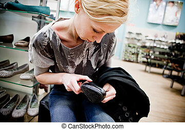Adult woman buying shoes in a store