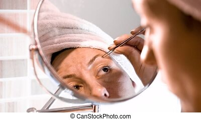 Adult woman corrects eyebrows and looking in the mirror -...