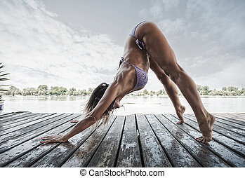 adult  woman doing yoga in bikini on wooden river raft