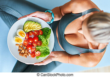 Adult woman eating healthy lunch and sitting on yoga mat