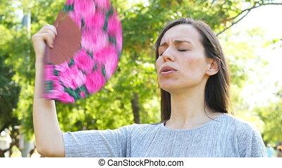 Adult woman fanning suffering heat stroke - Adult woman...