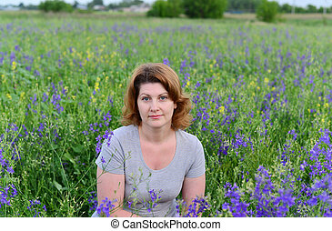 Adult woman in meadow with wild flowers