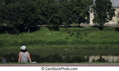 Adult woman in panama sitting on the river bank, resting, breathing air