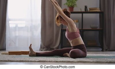 adult woman is training alone at home at morning, lady is stretching body, sitting on floor, full-length shot in living room