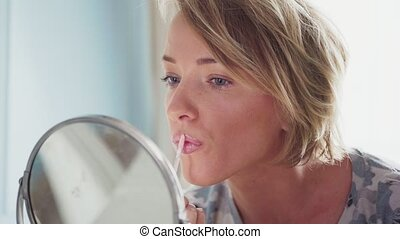 Adult woman makes makeup applying lipstick and looking in...