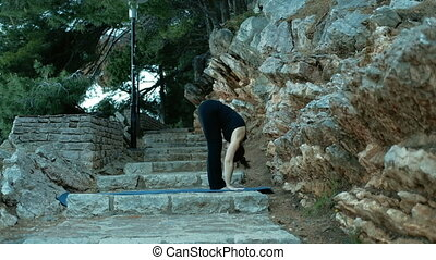 Adult woman performs a series of exercises on yoga in the rock.