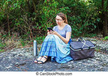 Adult woman reading e-book outdoors