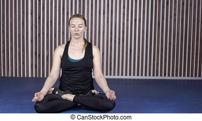 Adult woman sits in a lotus pose with her eyes closed at striped wall.