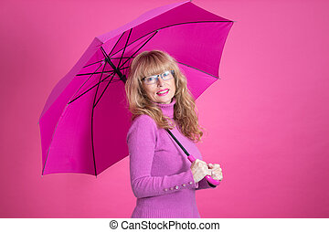 adult woman smiling with open umbrella over color background